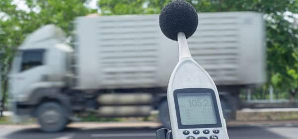 Foto van geluidsmeter met voorbijrazende vrachtwagen