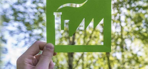 Afbeelding van hand die groen plaatje met fabriek vasthoud met op de achtergrond een bos